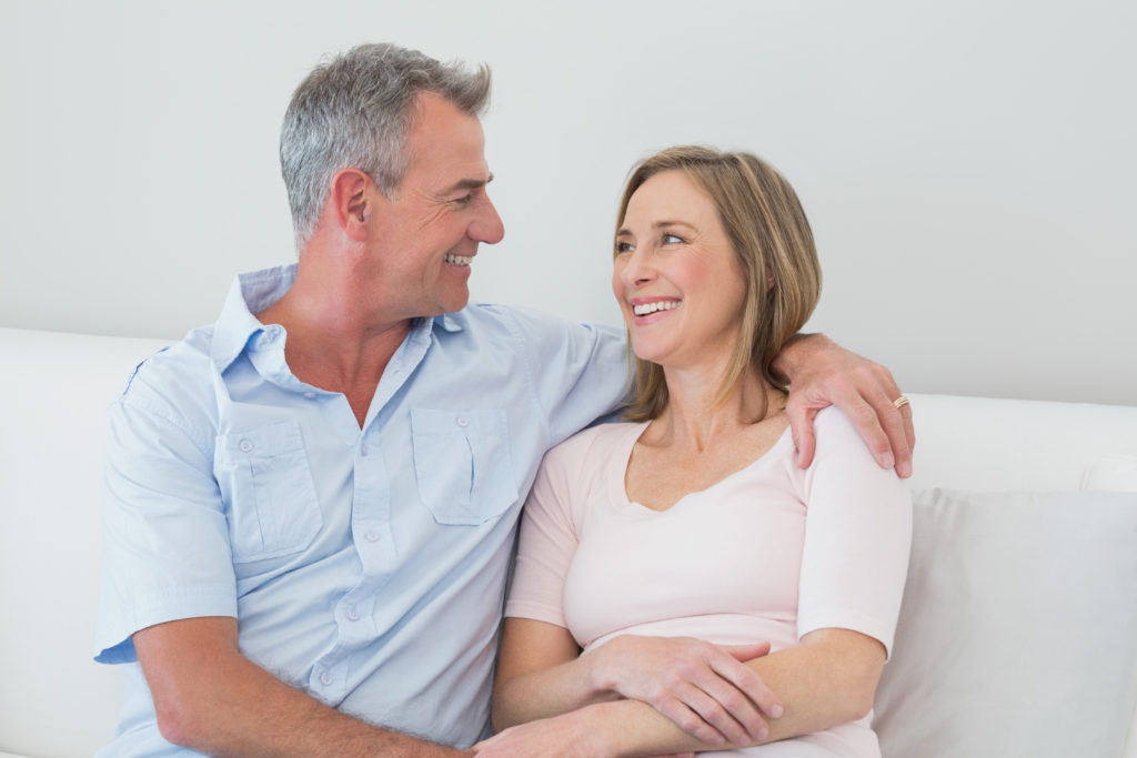 Happy relaxed couple sitting on sofa with arm around at home
